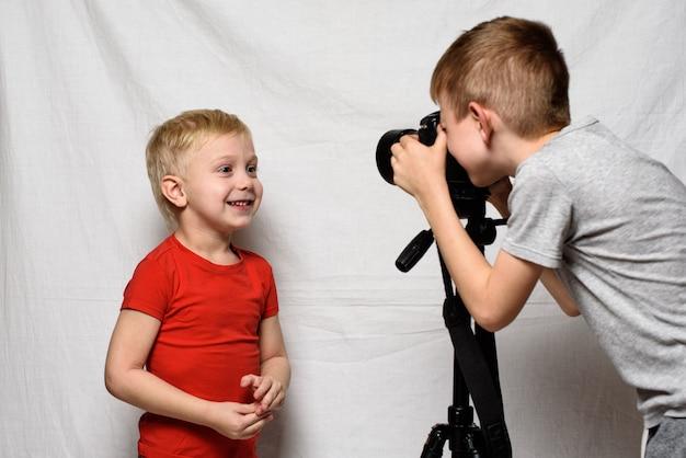 少年たちは一眼レフカメラでお互いを撮影しています。ホームスタジオ。若いブロガー