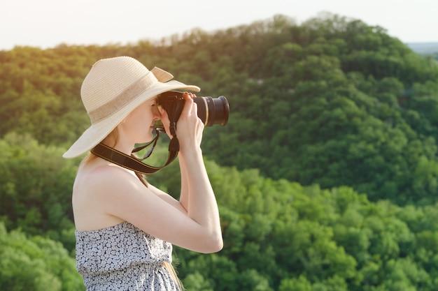 Женщина в шляпе фотографирует зеленую гору. вид сбоку