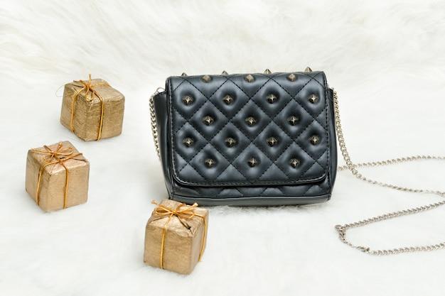 Маленькая черная сумка и подарочная коробка на белом меху праздничные покупки