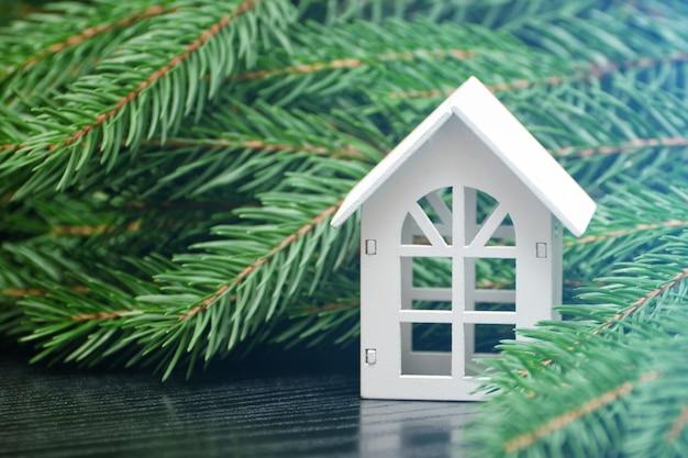 緑のモミの枝の背景に白い家