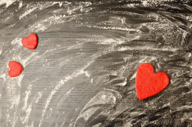 散った小麦粉の黒いテーブル。フレームの隅にある生地の赤いハート、