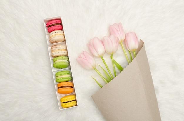 Коробка из разноцветных миндальное печенье и розовые тюльпаны на белом меху, вид сверху