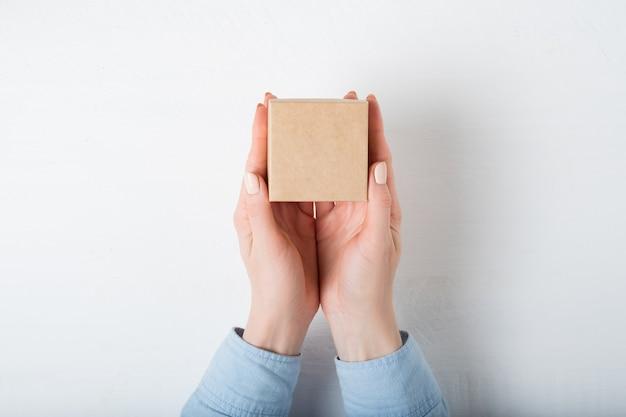女性の手で小さな正方形の段ボール箱。