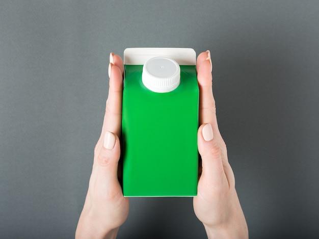 緑のカートンボックスまたはテトラパックのパッケージに女性の手でキャップ。
