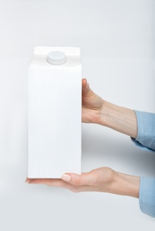 白い箱または女性の手にキャップのあるテトラパックの包装。