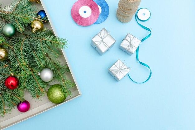 ギフトボックス、小ぎれいなな枝、装飾品。青色の背景。