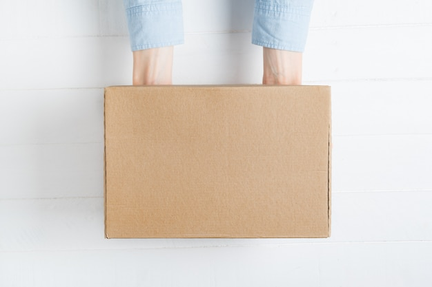 女性の手で長方形の段ボール箱。