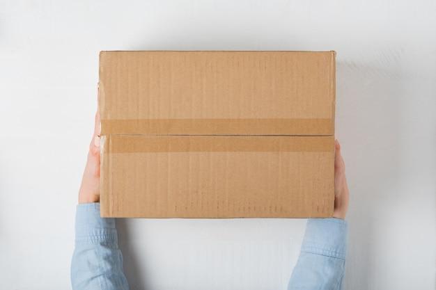 女性の手で大きな正方形の段ボール箱。