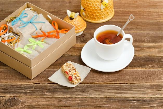 Чайная кружка, упаковка батончиков и сахарница. деревянный стол