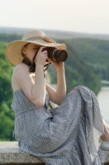 サンドレスとカメラと帽子の少女。遠くの緑の森と川