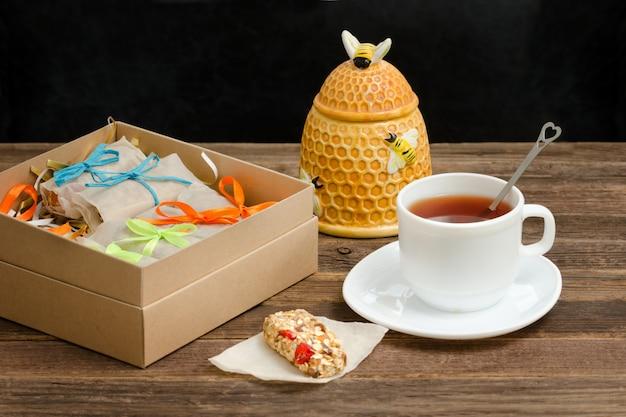 Чайная кружка, упаковка батончиков и сахарница.
