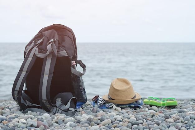 小石のビーチでのバックパック、帽子、服