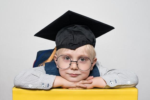 大きなメガネ、アカデミックハット、バックパックでかわいい金髪の少年の肖像画
