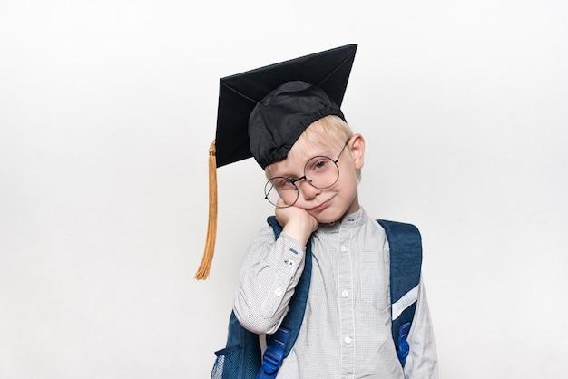大きなメガネ、アカデミックハット、スクールバッグで物思いにふける金髪の少年の肖像画