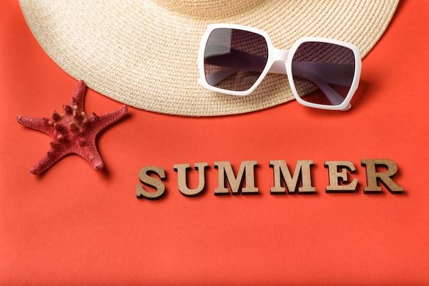 木製の手紙から単語夏。サングラス、帽子の一部、ヒトデ。サンゴのライブ背景。旅行のコンセプト