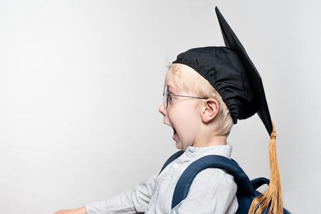 メガネ、アカデミックハット、白い背景の上のカバンに驚いた金髪少年の肖像画。学校のコンセプト