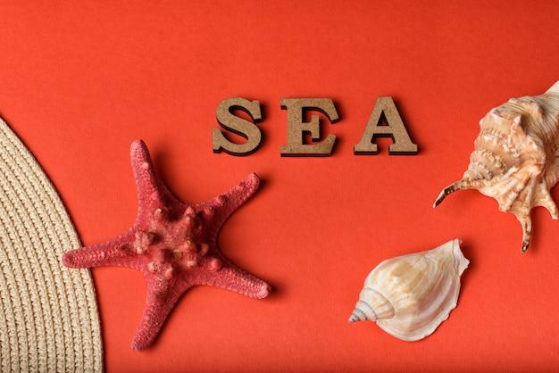 木製の手紙から単語海。貝殻、ヒトデ、帽子の一部。サンゴのライブ背景。マリンコンセプト