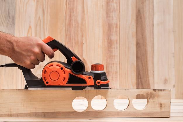 Электрический рубанок в мужской руке. обработка заготовки на светло-коричневом деревянном столе. вид сбоку, копия пространства