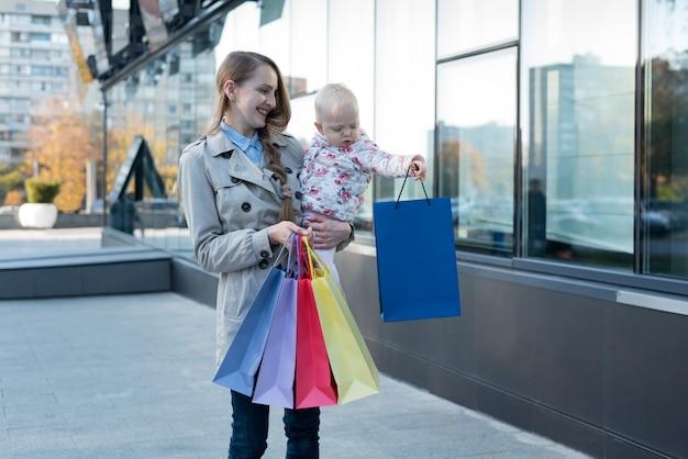 腕と買い物袋を手に小さな娘と幸せな若い母。買い物の日。