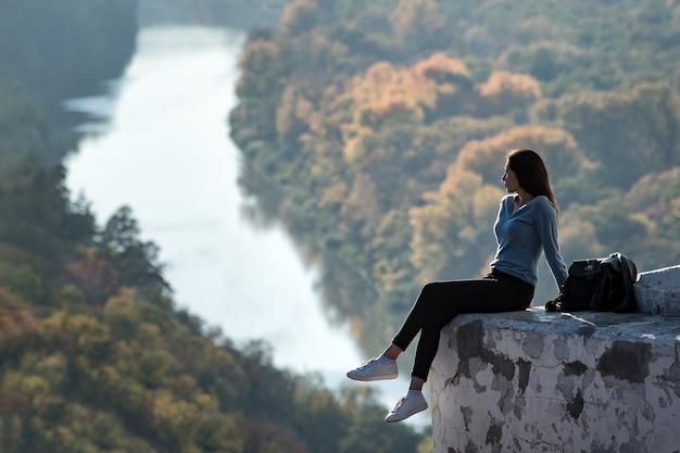 Красивая женщина сидит на холме и смотрит вдаль. наслаждение природой