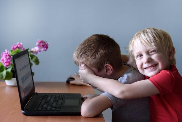 微笑む少年は、ラップトップを使用している友人に彼の目の上に手を置きます。危険なコンテンツ。子供とガジェット。