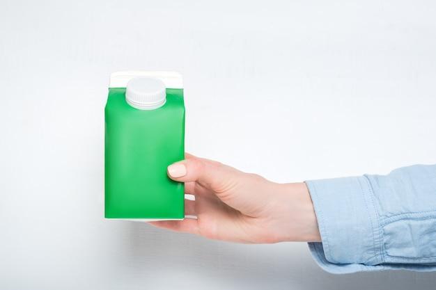 女性の手にキャップが付いた緑色のカートンボックスまたはテトラパックの包装。