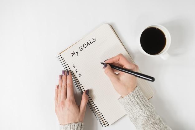 ノート、テーブルの上のコーヒーのマグカップ、トップビューで私の目標を書く女性の手