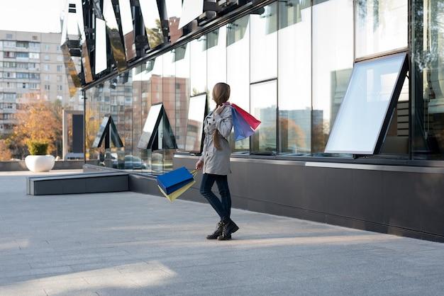Счастливая молодая женщина шопоголика с красочными сумками возле торгового центра, гуляя по улице.