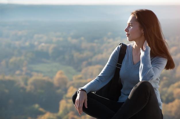 Портрет красивой девушки сидит на холме и смотрит вдаль.