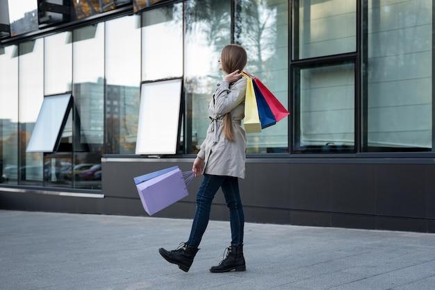 Счастливая молодая женщина шопоголика с красочными сумками возле торгового центра. прогулка по улице.