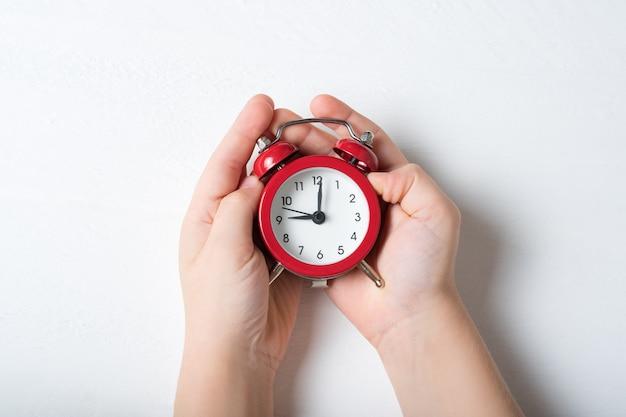 白い表面上の子供の手に赤い目覚まし時計