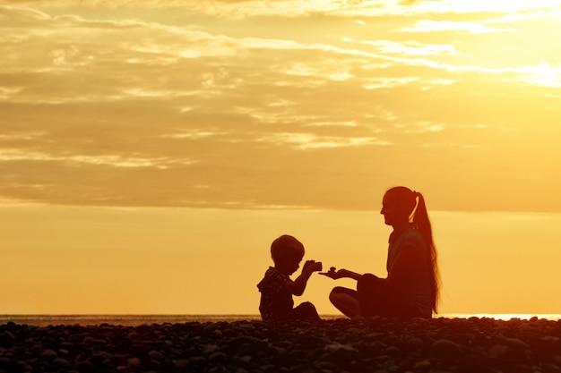 ママと息子が石とビーチで遊んでいます。日没時間、シルエット