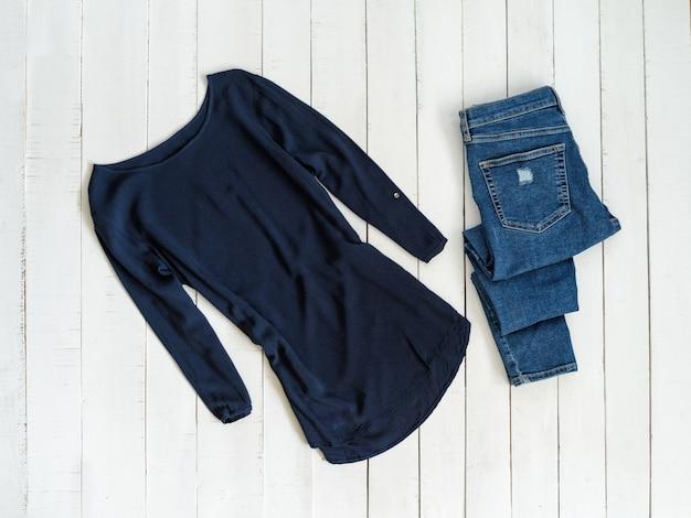 服ファッションのコンセプト。青いシャツと白い木製の背景にジーンズ。上面図