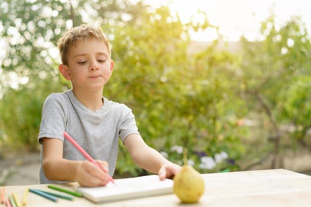 かわいい男の子は鉛筆で静物画を描きます。オープンエア。バックグラウンドでの庭。創造的なコンセプト。