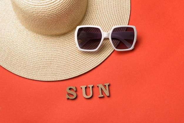 木製の手紙から単語の太陽。サングラスと帽子。サンゴのライブ背景。旅行のコンセプト