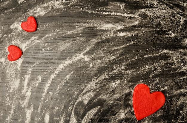 散った小麦粉の黒いテーブル。フレームの隅にある生地の赤いハート、テキストのための場所