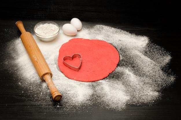 黒いテーブルの上に切り取ったハートと小麦粉を形成する赤い生地、麺棒。上面図