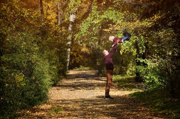 父は息子を投げます。秋の森。一緒に遊ぶ