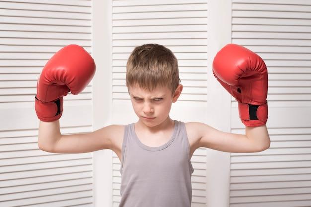 赤いボクシンググローブで怒っている少年。