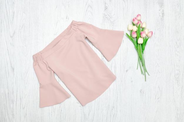 ファッションのコンセプト。ピンクのブラウスとピンクのチューリップ。ウッドの背景
