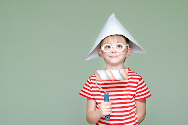 Мальчик в бумажной шляпе и очках. портрет. ролик для покраски
