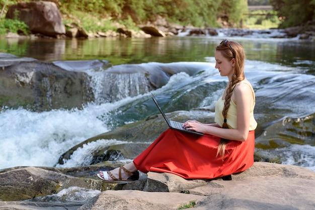 岩、山川のカスケードの上に座ってラップトップで赤いスカートの美しい長髪の女性。フリーランスのコンセプト。自然の中で働く