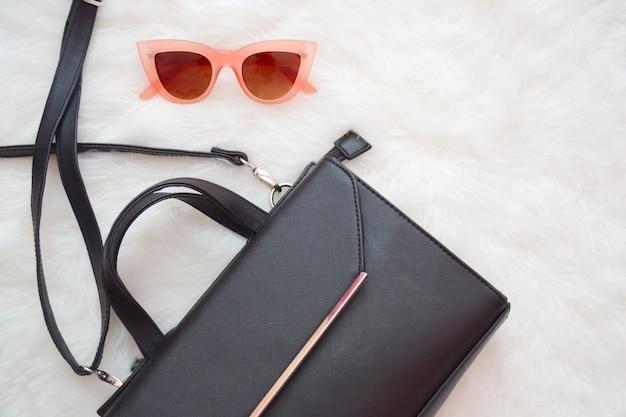 Черная сумочка и розовые очки на белом меху