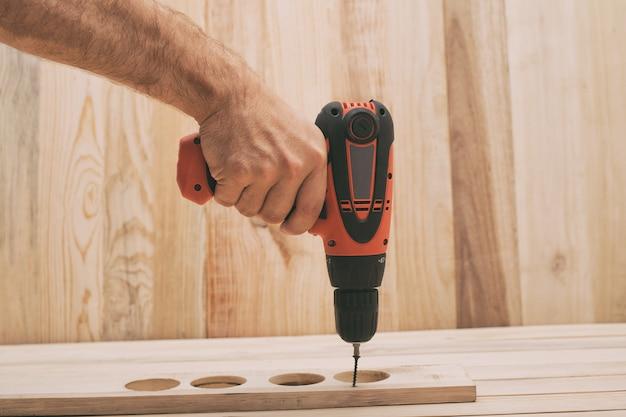 Электрическая дрель отвертка в мужской руке. затяжка винта, обработка заготовки на светло-коричневом деревянном столе.