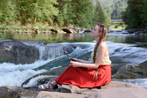 赤いスカートで物思いにふける美しい長い髪の女性は、山の川のカスケードに対して石の上にラップトップで座っています。フリーランスのコンセプト。自然の中で働く