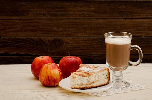 Яблочный пирог, капучино и спелые яблоки на деревянном столе