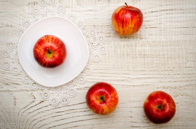 Яблоко на блюдце спелых яблок