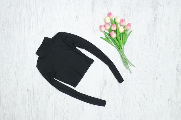 黒のタートルネック、チューリップの花束。ファッショナブルなコンセプト