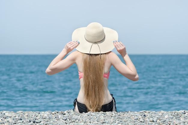 Красивая девушка в шляпе и купальник сидит на пляже. море на заднем плане. вид со спины
