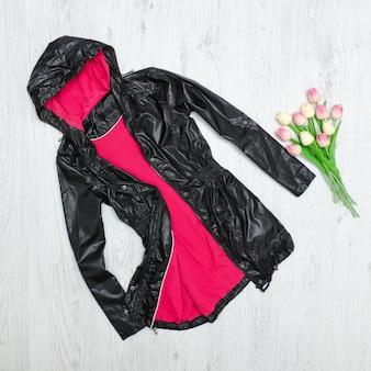 黒マントとチューリップの花束。ファッショナブルなコンセプト
